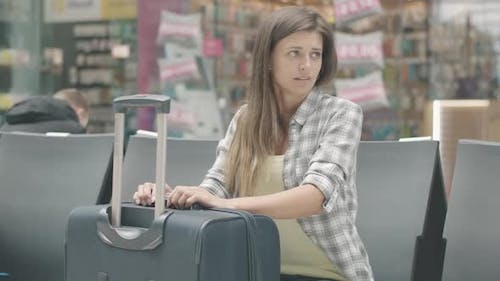 Portrait of Bored Young Caucasian Woman Sitting with Baggage in Waiting Area. Brunette Tourist Wait