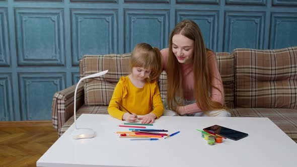 Cute Small Child Kid Daughter Learning Drawing Homework with Young Mother Home Distance Education