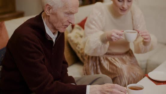 Thumbnail for Woman Pouring Black Coffee In Cup For Grandfather During Christmas