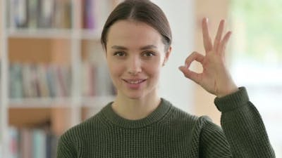 Ok Sign By Positive Young Woman