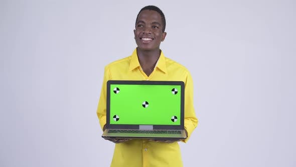 Thumbnail for Young Happy African Businessman Thinking While Showing Laptop
