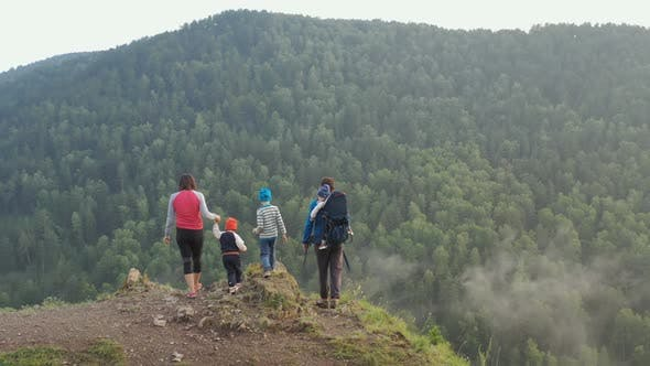 Thumbnail for Young Parents with Three Children Climb To the Top of the Mountain and Enjoy the Beautiful View