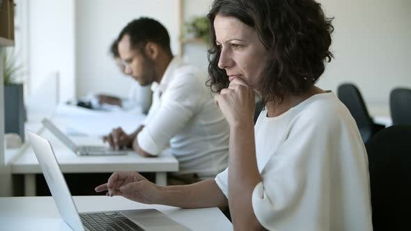 Thumbnail for Side View of Focused Caucasian Woman Typing on Laptop
