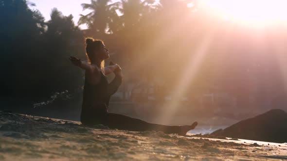 Thumbnail for Junge aufregende Frau in schwarz Trainingsanzug sitzt auf Sand Beach