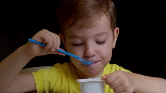 Closeup of a Baby Sitting at the Table and Eating Baby Food with a Spoon on Its Own