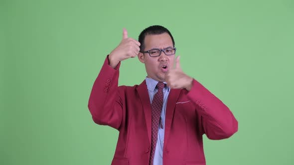 Cover Image for Happy Asian Businessman with Eyeglasses Giving Thumbs Up and Looking Excited