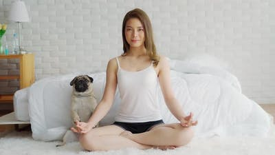 Asian woman practice yoga lotus pose with dog pug breed enjoy and relax with yoga