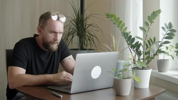 Man with a Beard Uses a Computer