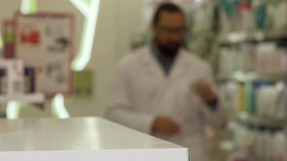 Thumbnail for Pharmacist Putting Blisters of Pills on the Counter Working at His Drugstore