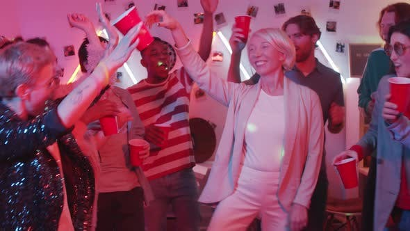 Thumbnail for Happy Elderly Woman Dancing with Young People at House Party