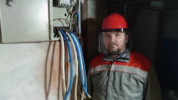 Electrician wearing hard hat and face shield to protect eyes and face.