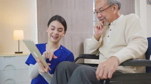 Asian Senior elderly male patient on wheelchair talking to physician nurse at nursing home care.