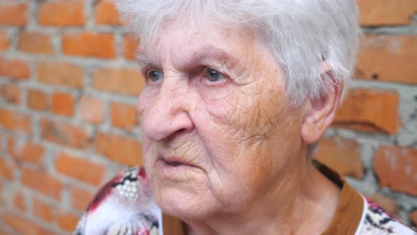 Cover Image for Grandmother Sitting Outdoor and Talking with Somebody. Portrait of Elderly Woman with Serious Facial