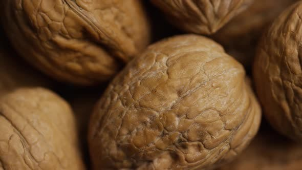 Cinematic, rotating shot of walnuts in their shells on a white surface - WALNUTS