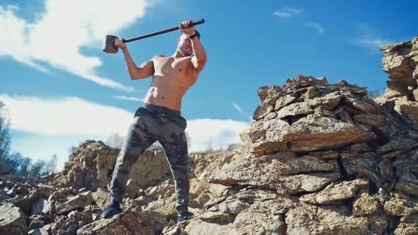 Thumbnail for Muscular athlete with hammer on the rocks