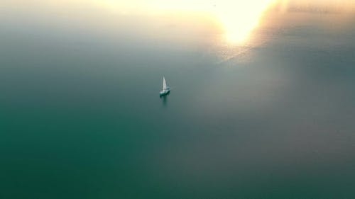 Aerial View One Yacht at Sunset in the Open Sea. Flight at Sunset Near the Yacht with a Sail View