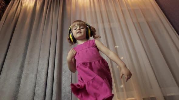 Thumbnail for Little Child Girl in Wireless Headphones Enjoying Listen Music. Dancing at Home