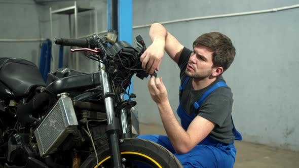 Mechanic Tries To Repair a Motorcycle in Auto Repair Shop