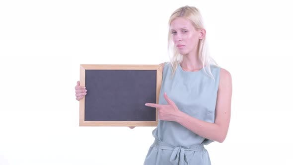 Thumbnail for Stressed Young Blonde Woman Holding Blackboard and Giving Thumbs Down