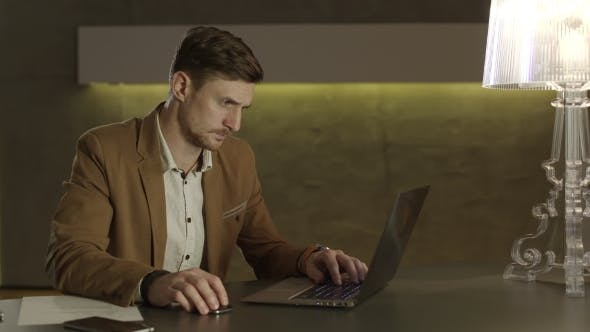 Thumbnail for Businessman Looking With Interest At His Laptop Computer.