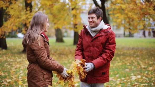 Happy Young Couple Throwing Autumn Leaves In Park 10