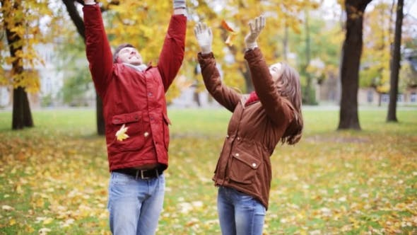 Happy Young Couple Throwing Autumn Leaves In Park 15