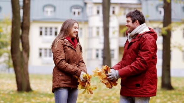 Happy Young Couple Throwing Autumn Leaves In Park 30