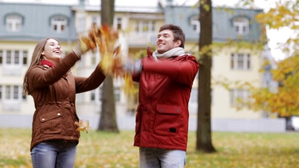 Happy Young Couple Throwing Autumn Leaves In Park 31