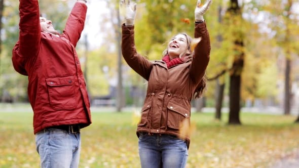 Happy Young Couple Throwing Autumn Leaves In Park 32