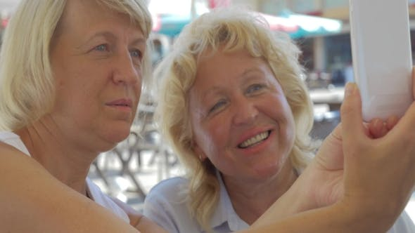 Thumbnail for Middle-aged Blond Women Smiling, Looking In Smartphone And Making Selfie