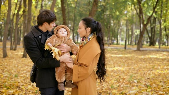 Thumbnail for Family In The Forest. Baby Boy With Autumn Leaves In His Hand, In The Arms Of  Father's.