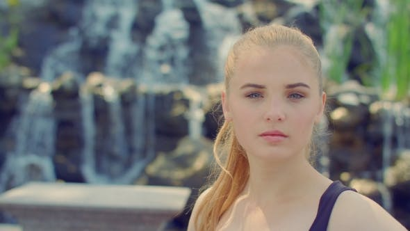 Thumbnail for Blonde Woman Posing In Park. Young Woman Portrait Near Waterfall