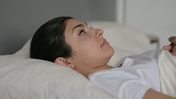 Indian Woman Laying Awake in Bed