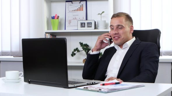 Thumbnail for Businessman Talking On Phone In His Office And Smiling