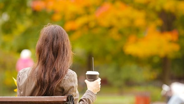 Thumbnail for Beautiful Woman Drinking Coffee In Autumn Park Under Fall Foliage