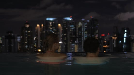 Thumbnail for In Pool On Roof Of a Hotel In Kuala Lumpur, Malaysia Couple In Love Looking To Night City