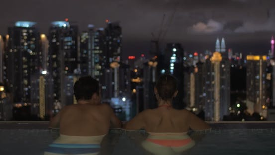 Thumbnail for In Pool On Roof Of a Hotel In Kuala Lumpur, Malaysia Man With Woman Looking To Night City