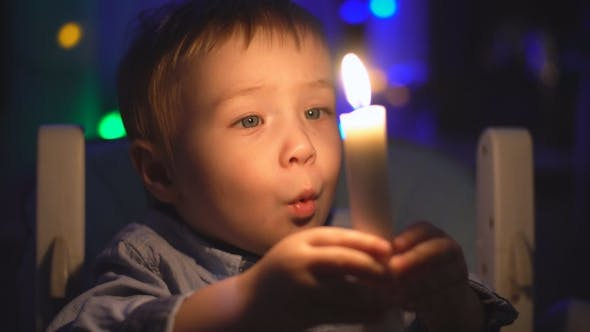 Boy Blows Out Candle