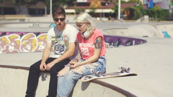 Thumbnail for Young Couple Of Skateboarders Sitting Chatting