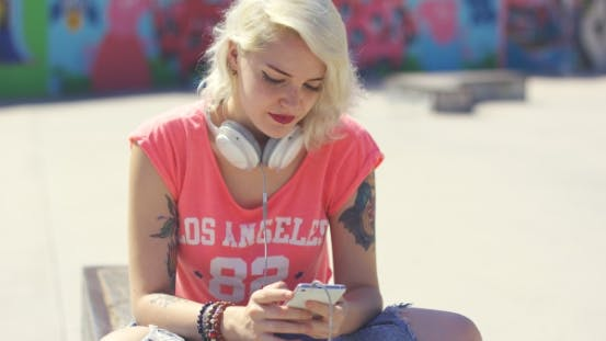 Thumbnail for Young Woman Searching For Tunes On Her Mobile