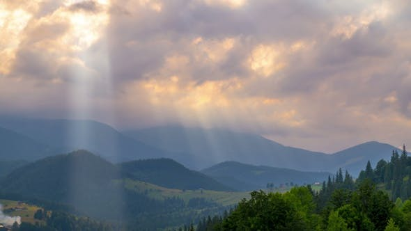 Thumbnail for Sun Rays Pass through the Clouds Over the Mountains at Sunset.