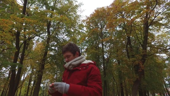 Thumbnail for Young Man With Smartphone Walking At Autumn Park