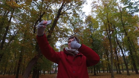 Cover Image for Man With Smartphone Taking Video At Autumn Park