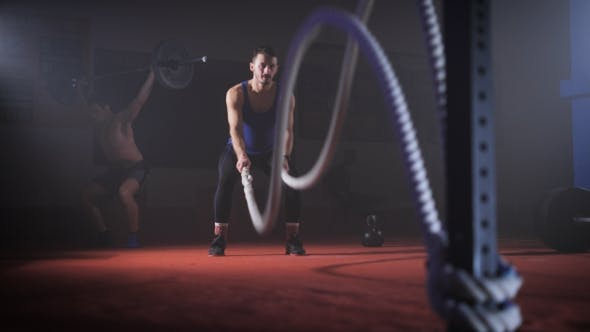 Thumbnail for Fit Young Man Holds Rope In His Hands And Makes Heavy Rope Training Workout.