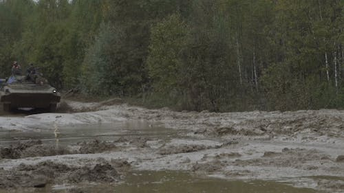 Military Armored Personnel Carrier Travels Along The Muddy Road. Dirty Armored Vehicle