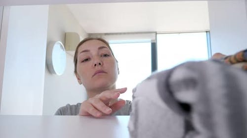 Young Woman Is Putting Clothes in Wardrobe Cleaning in Her Home.