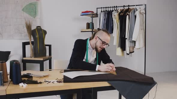 Thumbnail for Young Bearded Fashion Designer Draw Sketches Using Ruler, Cut out Cloth