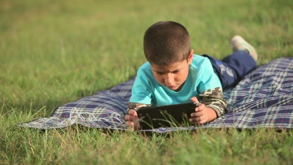 Thumbnail for Boy Playing On The Lawn With a Tablet