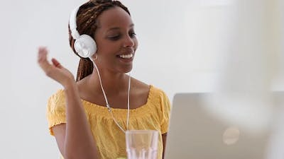 Young Woman in Headphones Talk and Gesture in Video Call