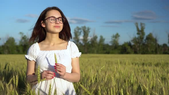 Thumbnail for A Young Woman in a White Dress Stands in a Green Wheat Field and Holds a Spikelet in Her Hands. The